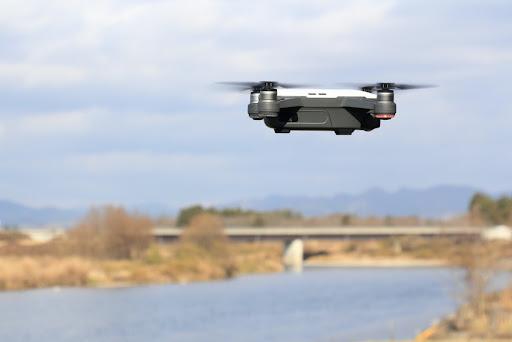 川の上を飛ぶドローン