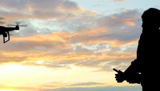 ドローンを操縦する男性と夕日